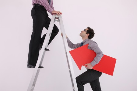Businessman standing on the ladder, another businessman climbing up while holding arrow sign photo