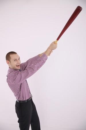 Businessman swinging baseball bat photo