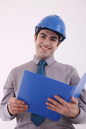 Businessman with safety helmet smiling while holding document photo