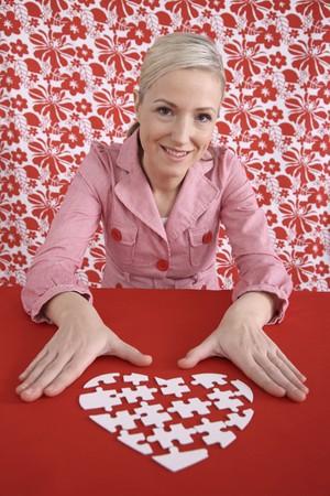 Woman making heart shaped puzzle photo
