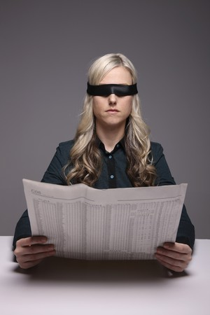 Blindfolded businesswoman reading newspaper photo