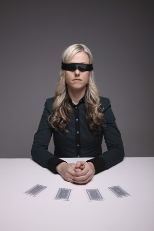 blindfolded: Blindfolded businesswoman playing with cards