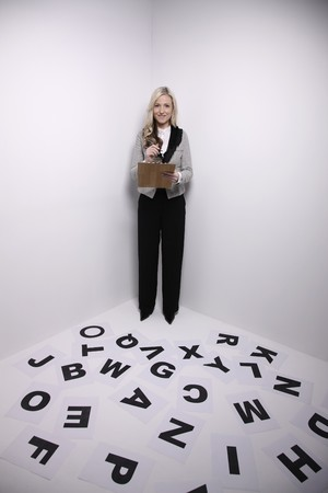 Businesswoman standing in corner, holding pen and clipboard photo