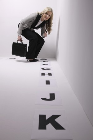 Businesswoman looking at alphabets on the floor through a magnifying glass photo