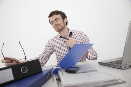 Man pulling down his tie looking stressed photo