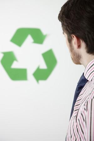 Man looking at recycling symbol photo
