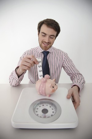 Man putting dollar note into piggy bank Stock Photo - 6990909