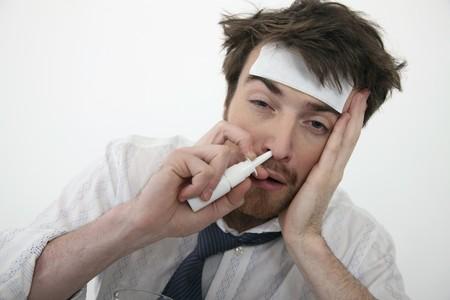 north western european descent: Man putting nasal spray drop into his nose Stock Photo