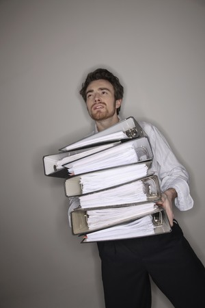 Man carrying a stack of files photo