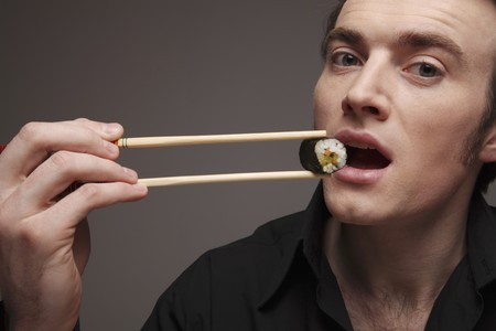 Man eating sushi with chopsticks