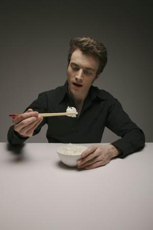 Man eating white rice with chopsticks Stock Photo - 6990926