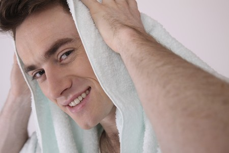 Man wiping his hair with towel photo
