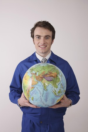 Man holding globe with both hands smiling photo