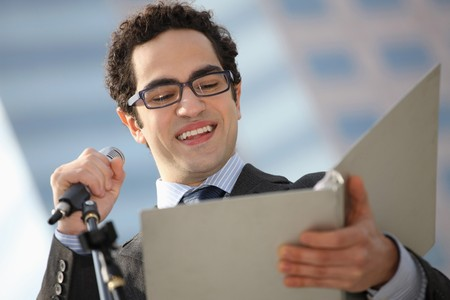 Businessman reading speech from document photo