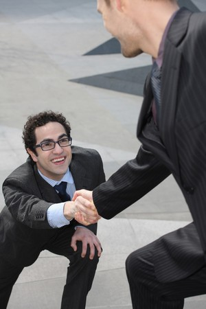 personas ayudando: Empresario ofreciendo mano extendida a otro empresario Foto de archivo