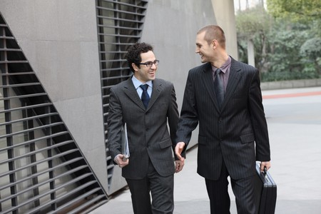 southern european descent: Businessmen chatting while walking
