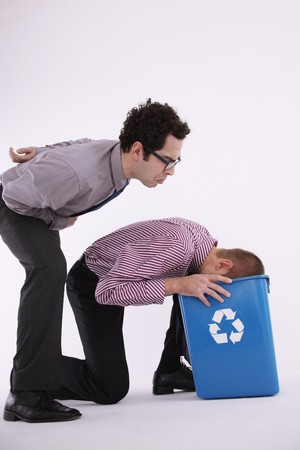 Businessman watching man putting his head into the recycling bin photo
