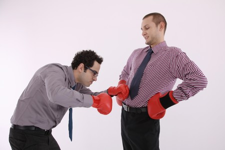 Businessman with boxing gloves checking man's tummy photo