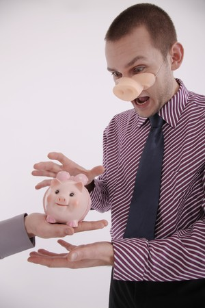 Businessman with pigs snout looking at piggy bank with his mouth opened photo