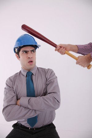 Businessman with safety helmet sitting with his arms folded, hand with baseball bat about to hit his head photo