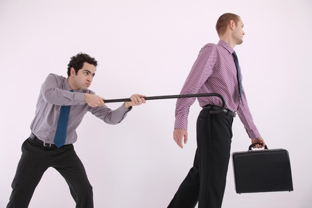 Businessman trying to pull another businessman with a cane photo