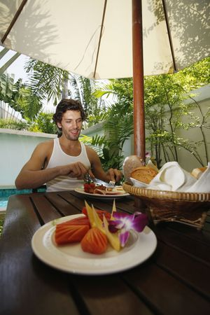 Man having breakfast by the pool Stock Photo - 6925045