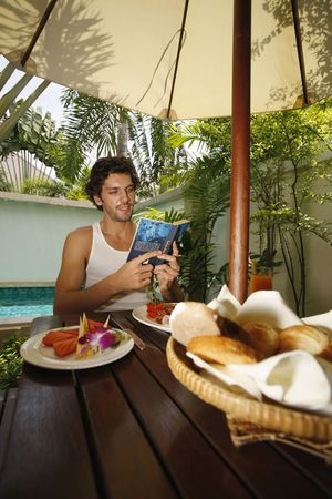 Man reading book with breakfast on the table Stock Photo - 6925049
