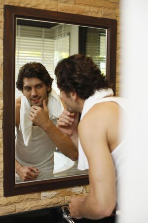Man examining himself in front of the mirror Stock Photo - 6925062
