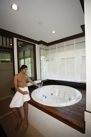 Man filling water into hot tub photo