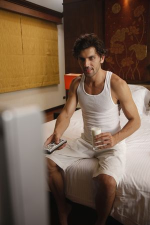 Man holding a glass of milk while watching television Stock Photo - 6925072