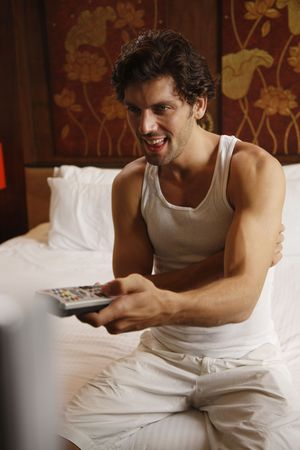 Man with remote control in hand watching television Stock Photo - 6925073