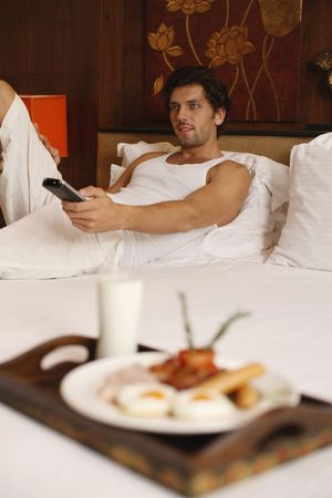 Man watching television with breakfast on bed Stock Photo - 6925064