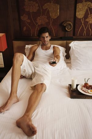Man watching television with breakfast on bed Stock Photo - 6925075