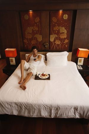 Man watching television with breakfast on bed Stock Photo - 6925077