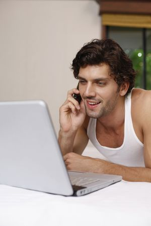 Man using laptop while talking on the phone photo