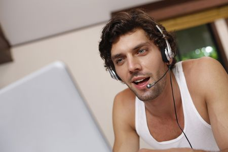 Man with headset using laptop Stock Photo - 6924997