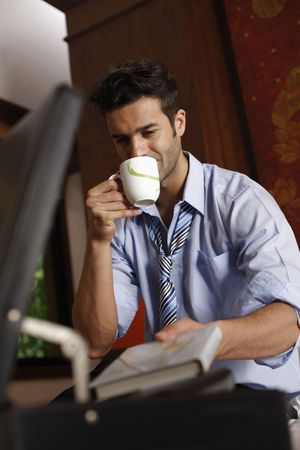 tomando refresco: Libro de la toma de empresario de malet�n mientras bebe caf� Foto de archivo