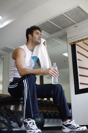 Man holding water bottle wiping his sweat photo