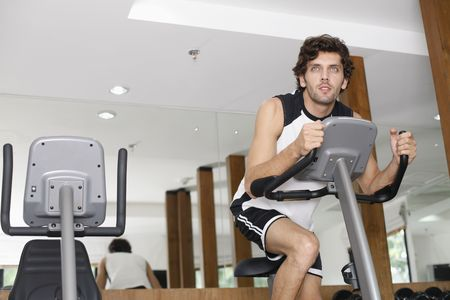 turkish ethnicity: Man on exercise bike at gym Stock Photo