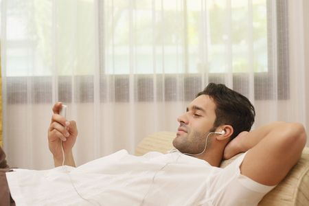 portable mp3 player: Man listening to music on portable mp3 player Stock Photo
