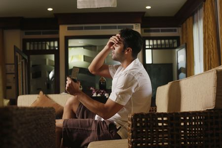 Man with hand on his forehead after watching television Stock Photo - 6935510