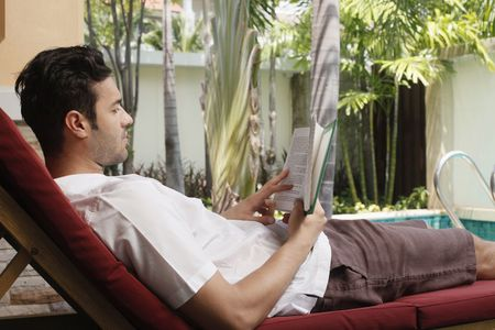 Man reading book on lounge chair photo