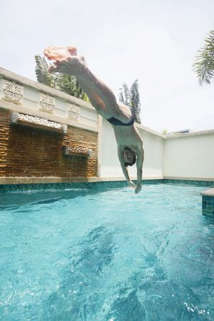 Man diving into swimming pool photo