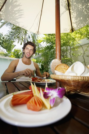 Man having breakfast by the pool Stock Photo - 6974158