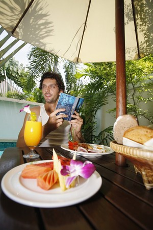 Man reading book with breakfast on the table Stock Photo - 6974159