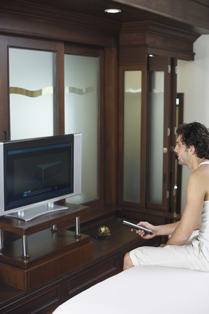 Man with remote control in hand watching television Stock Photo - 6974167