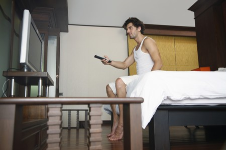 Man with remote control in hand watching television Stock Photo - 6974168