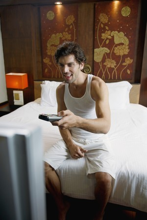 Man with remote control in hand watching television Stock Photo - 6974171