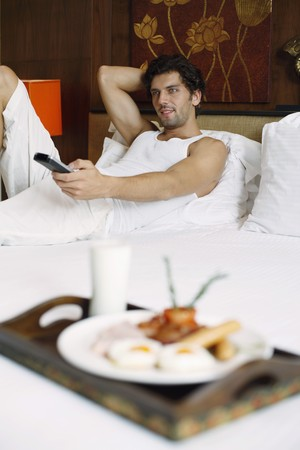 Man watching television with breakfast on bed Stock Photo - 6974172