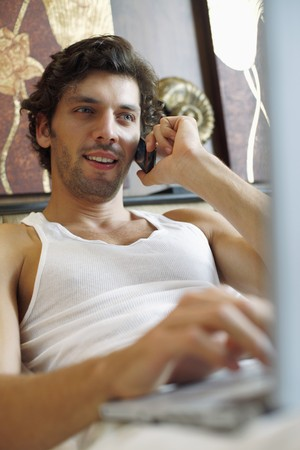 Man using laptop while talking on the phone Stock Photo - 6974176